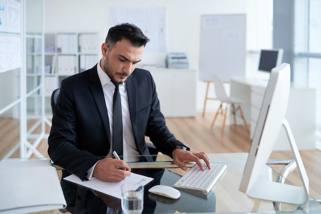 Kaukasischer mann im anzug, der im büro sitzt, an computer arbeitet und auf papier schreibt
