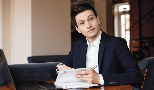 Kaukasischer mann im anzug, der jemanden ansieht, während er einen computer benutzt und einige notizen im buch macht