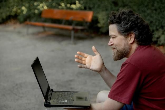 Kaukasischer mann im freizeitpark mit laptop, der eine videokonferenz macht