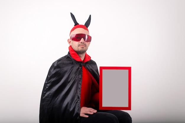 Kaukasischer mann im halloween-kostüm, der leeres typenschild über weißem studiohintergrund demonstriert.