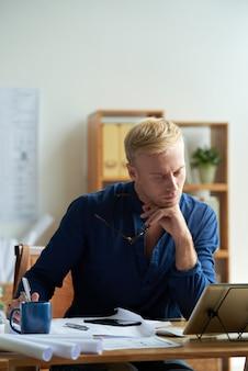 Kaukasischer mann im zufälligen hemd, das am schreibtisch im büro sitzt und tablette betrachtet