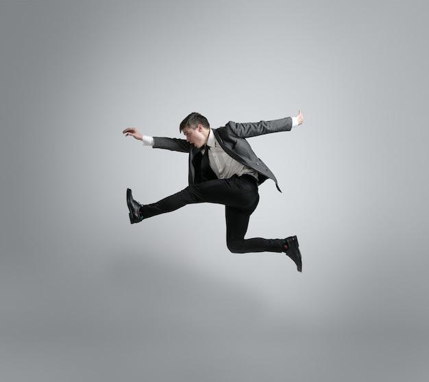 Kaukasischer mann in bürokleidung läuft lokalisiert auf grauem studiohintergrund