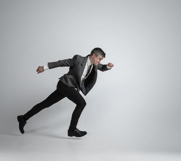 Kaukasischer mann in der bürokleidung, die wie ein professioneller sportler auf grauem hintergrund läuft.
