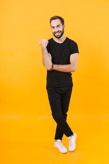 Kaukasischer mann in voller länge in grundkleidung lächelt und zeigt mit dem finger beiseite isoliert über gelber wand
