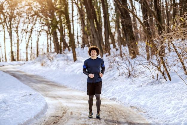 Kaukasischer mann in voller länge in sportbekleidung und mit lockigem haar auf der landstraße. winter. outdoor-fitness-konzept.