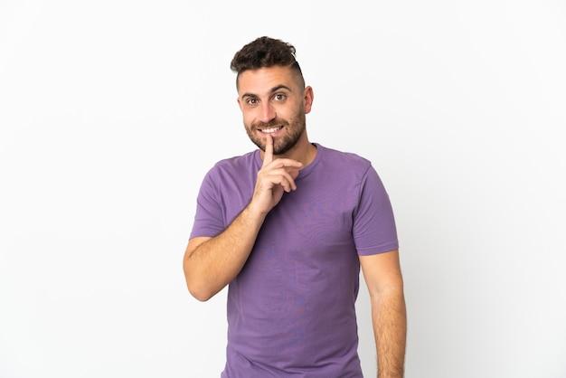 Kaukasischer mann isoliert auf weißem hintergrund, der ein zeichen der stille zeigt, geste, die finger in den mund steckt