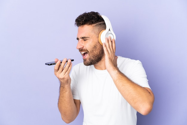 Kaukasischer mann lokalisiert auf lila hintergrund, der musik mit einem handy und gesang hört