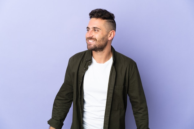 Kaukasischer mann lokalisiert auf lila hintergrund, der zur seite schaut und lächelt