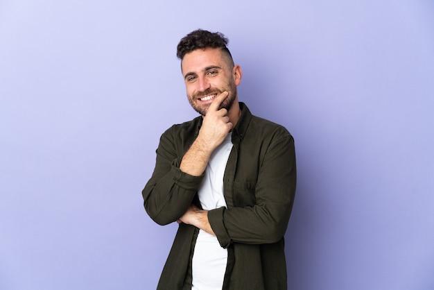Kaukasischer mann lokalisiert auf lila hintergrund glücklich und lächelnd