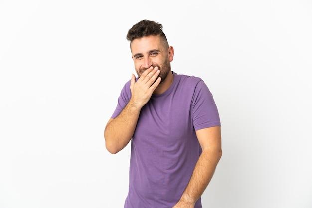 Kaukasischer mann lokalisiert auf weißem hintergrund glücklich und lächelnd, das mund mit hand bedeckt