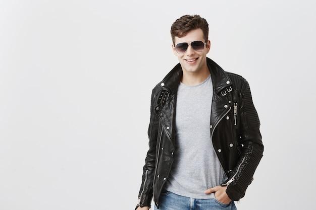 Kaukasischer mann mit ansprechendem blick, breit lächelnd mit weißen geraden zähnen, im haus posierend. stilvoller hübscher attraktiver mann mit trendigem haarschnitt in schwarzer lederjacke, mit sonnenbrille auf.