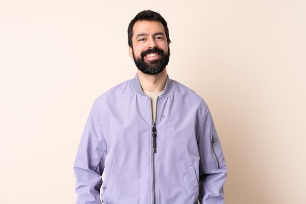 Kaukasischer mann mit bart, der eine jacke über isoliertem hintergrundlachen trägt