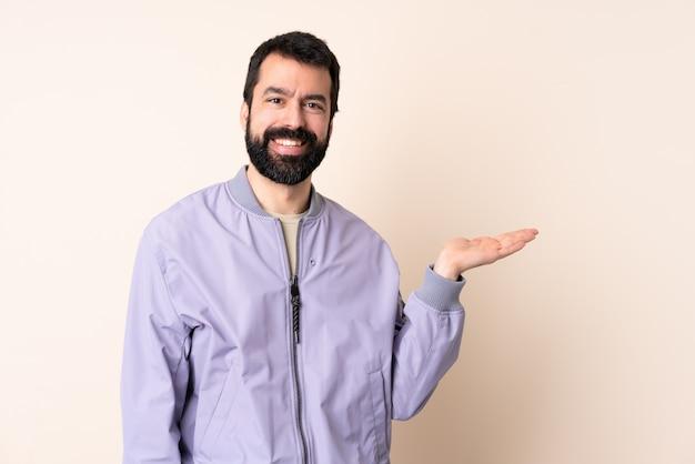 Kaukasischer mann mit bart, der eine jacke über isoliertem raum hält, der imaginären copyspace auf der handfläche hält, um eine anzeige einzufügen