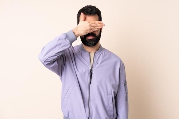 Kaukasischer mann mit bart, der eine jacke über isoliertem raum trägt, der augen durch hände bedeckt. ich will nichts sehen