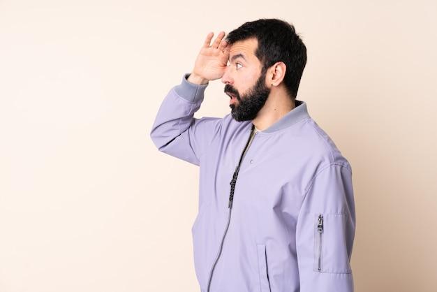 Kaukasischer mann mit bart, der eine jacke über lokalisiertem hintergrund mit überraschungsausdruck beim betrachten der seite trägt