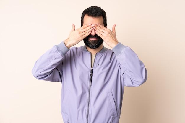 Kaukasischer mann mit bart, der eine jacke über lokalisiertem hintergrund trägt, der augen durch hände bedeckt und lächelt