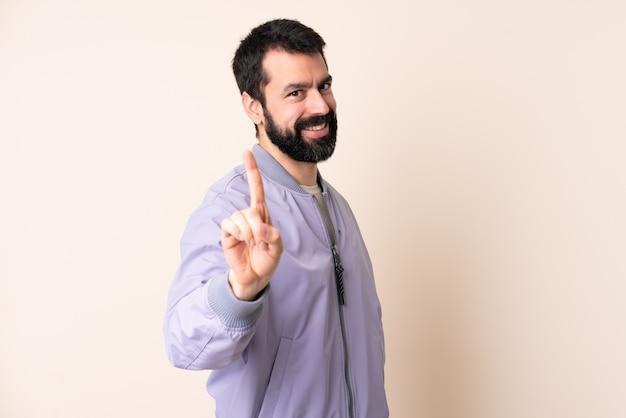 Kaukasischer mann mit bart, der eine jacke über lokalisiertem hintergrund trägt, der einen finger zeigt und anhebt
