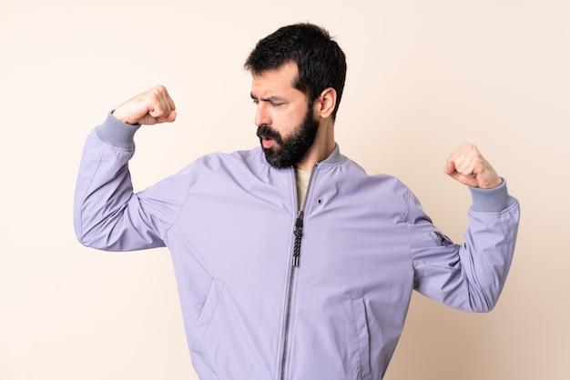 Kaukasischer mann mit bart, der einen isolierten hintergrund der jacke trägt, der starke geste tut