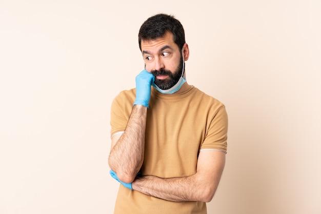 Kaukasischer mann mit bart, der mit einer maske und handschuhen über wand mit müdem und gelangweiltem ausdruck schützt