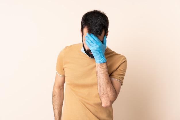 Kaukasischer mann mit bart, der mit einer maske und handschuhen über wand mit müdem und krankem ausdruck schützt