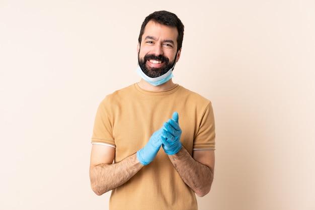 Kaukasischer mann mit bart, der mit einer maske und handschuhen über wand schützt, applaudiert nach präsentation in einer konferenz