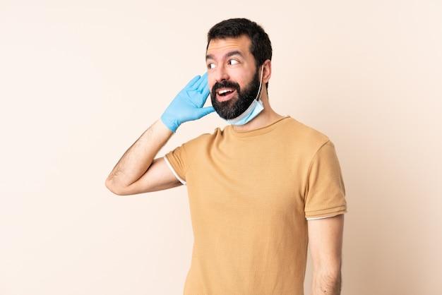 Kaukasischer mann mit bart, der mit einer maske und handschuhen über wand schützt, der etwas hört, indem man hand auf das ohr legt