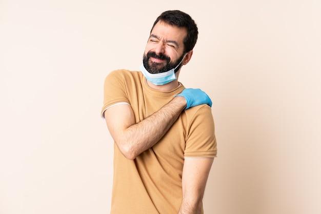 Kaukasischer mann mit bart, der mit einer maske und handschuhen über wand schützt, die unter schulterschmerzen leiden, weil sie sich bemüht haben