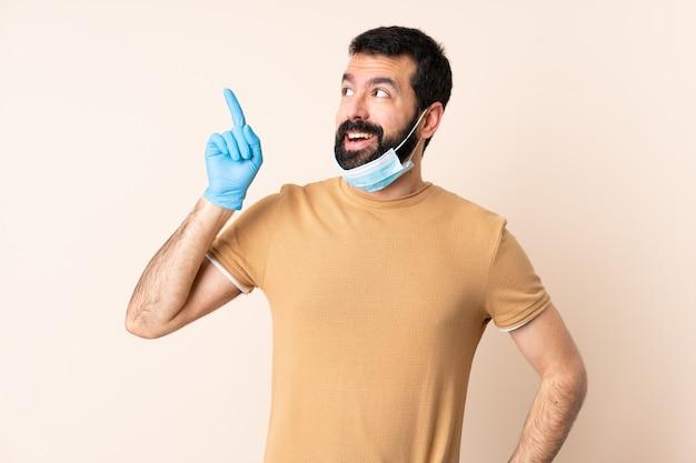 Kaukasischer mann mit bart, der mit einer maske und handschuhen über wand schützt, um die lösung zu realisieren, während er einen finger anhebt