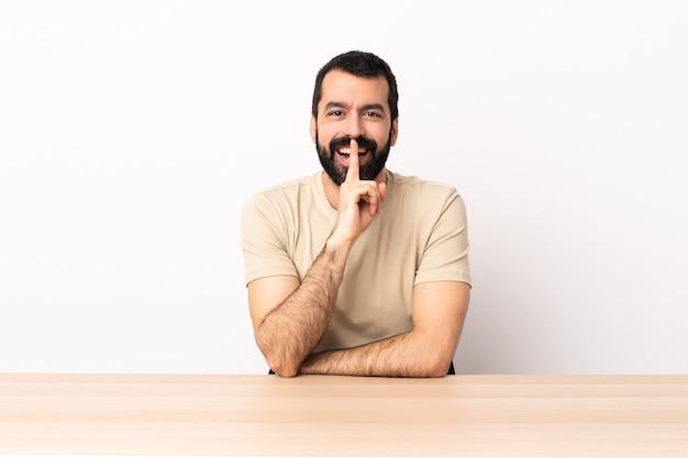 Kaukasischer mann mit bart in einem tisch, der ein zeichen der stille zeigt, geste, die finger in den mund steckt.