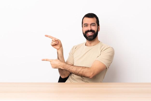 Kaukasischer mann mit bart in einem tisch, der mit dem finger zur seite zeigt und ein produkt präsentiert.