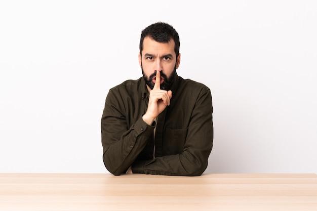 Kaukasischer mann mit bart in einer tabelle, die ein zeichen der stille zeigt