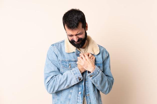 Kaukasischer mann mit bart über isoliertem hintergrund, der einen schmerz im herzen hat