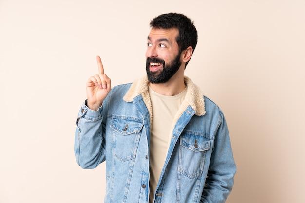 Kaukasischer mann mit bart über wand, der beabsichtigt, die lösung zu realisieren, während er einen finger anhebt