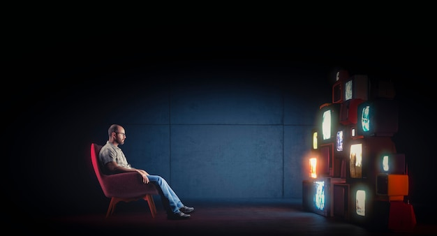Kaukasischer mann mit brille, die auf einem sessel sitzt und mehrere vintage-fernseher beobachtet