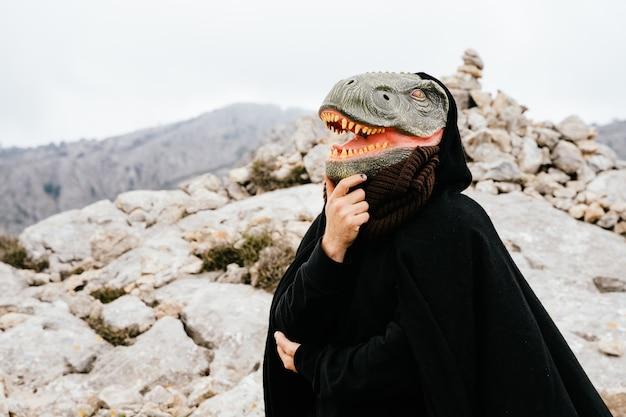 Kaukasischer mann mit dinosauriermaske und umhang, der die geste des denkens mit den händen auf dem kopf in der sierra de tramuntana, palma de mallorca, spanien macht