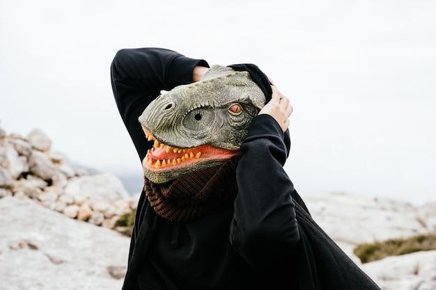 Kaukasischer mann mit dinosauriermaske und umhang überrascht, kreischt und hält seine hände an den kopf in der sierra de tramuntana, palma de mallorca, spanien