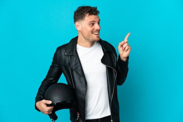 Kaukasischer mann mit einem motorradhelm lokalisiert auf blauer wand, der beabsichtigt, die lösung zu realisieren, während ein finger angehoben wird