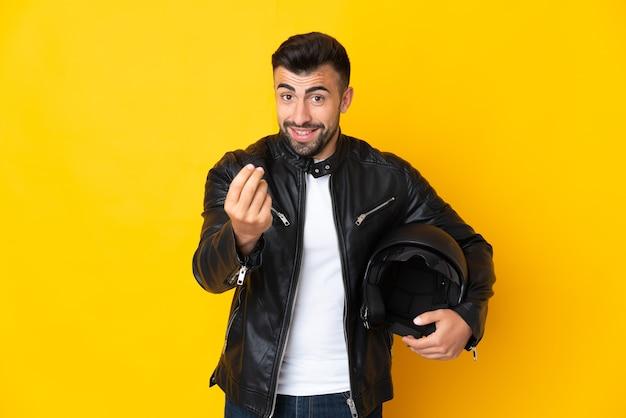 Kaukasischer mann mit einem motorradhelm über isolierter gelber wand, die geldgeste macht