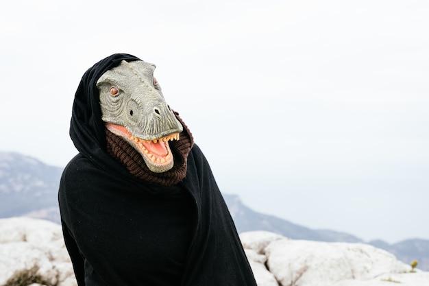 Kaukasischer mann mit einer dinosauriermaske und einem umhang, der mit seinem körper in der sierra de tramuntana, palma de mallorca, spanien, eine fragende geste macht