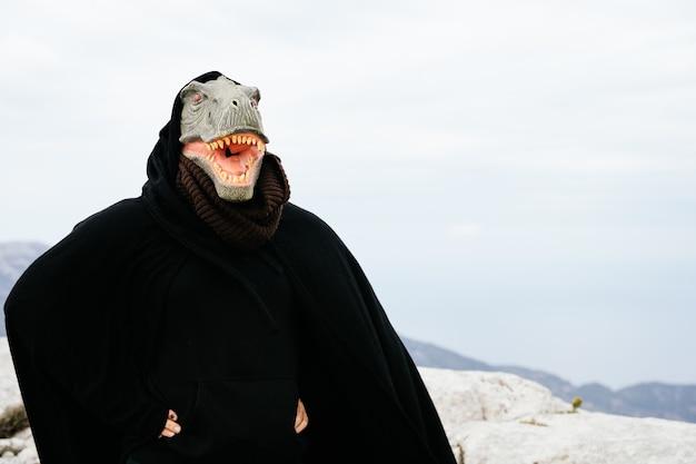 Kaukasischer mann mit einer dinosauriermaske und einem umhang, der mit seinem körper in der sierra de tramuntana, palma de mallorca, spanien, eine wütende geste macht
