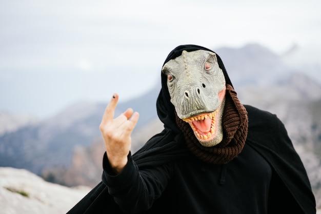 Kaukasischer mann mit einer dinosauriermaske und einem umhang, der mit seiner hand in der sierra de tramuntana, palma de mallorca, spanien, das zeichen der hörner macht?