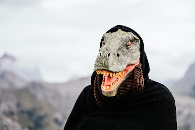 Kaukasischer mann mit einer lächelnden dinosauriermaske und einem umhang in der sierra de tramuntana. palma de mallorca, spanien