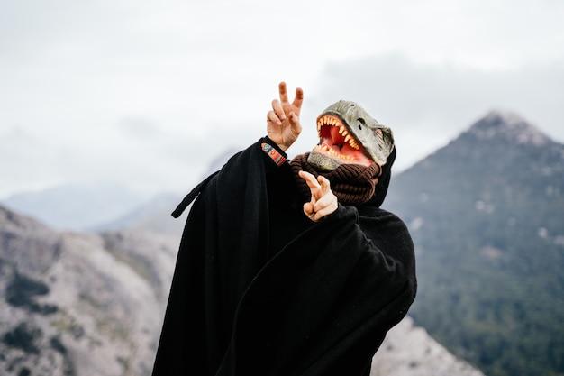 Kaukasischer mann mit einer wütenden dinosauriermaske und einem umhang in der sierra de tramuntana. palma de mallorca, spanien