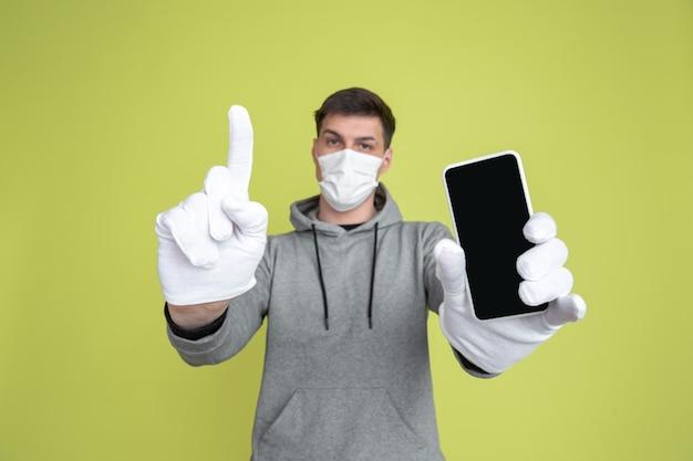 Kaukasischer mann mit gesichtsmaske, handschuhen und smartphone. covid konzept