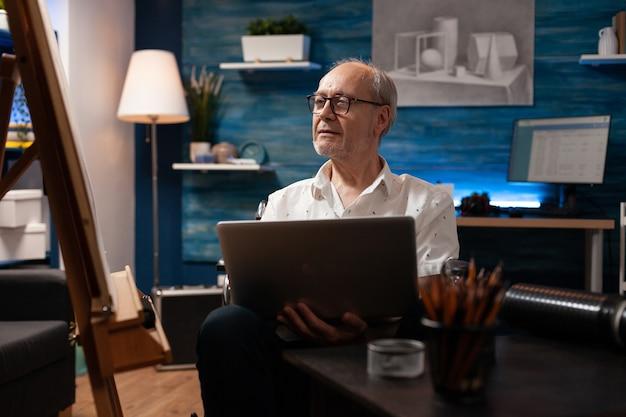 Kaukasischer mann mit handicap mit laptop zum zeichnen
