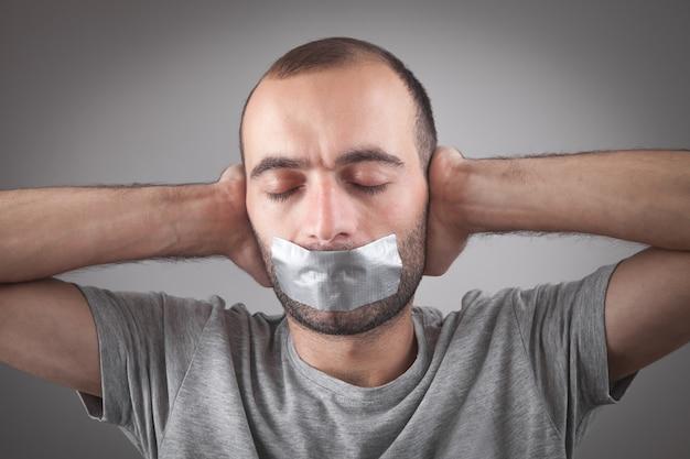 Kaukasischer mann mit klebeband auf mund. zensur