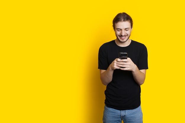 Kaukasischer mann mit langen haaren und borsten, der mit jemandem auf einer gelben wand mit freiem raum plaudert