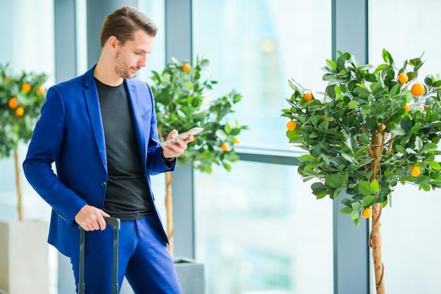Kaukasischer mann mit mobiltelefon am flughafen beim warten auf einstieg