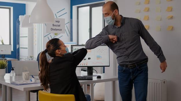 Kaukasischer mann mit schützender gesichtsmaske zur vermeidung von coronavirus, der den ellbogen mit seinem kollegen berührt, während er an einem technologieprojekt arbeitet, das während der sperrung von covid19 am tisch im geschäftsbüro sitzt
