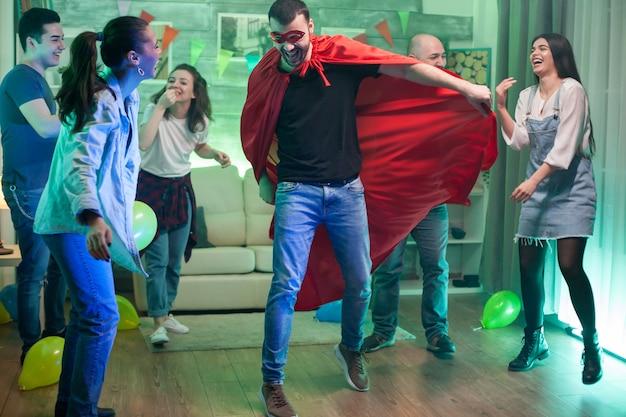 Kaukasischer mann mit superhelden-kostüm, der auf der party von freunden in die luft springt.